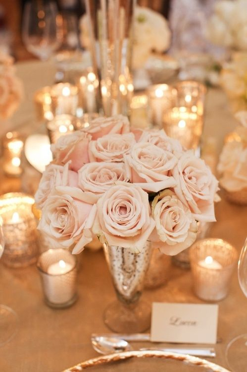Blush tone rose bouquet serves as a floral centerpiece, love that it's surrounded with candles! how romantic for a pink wedding.