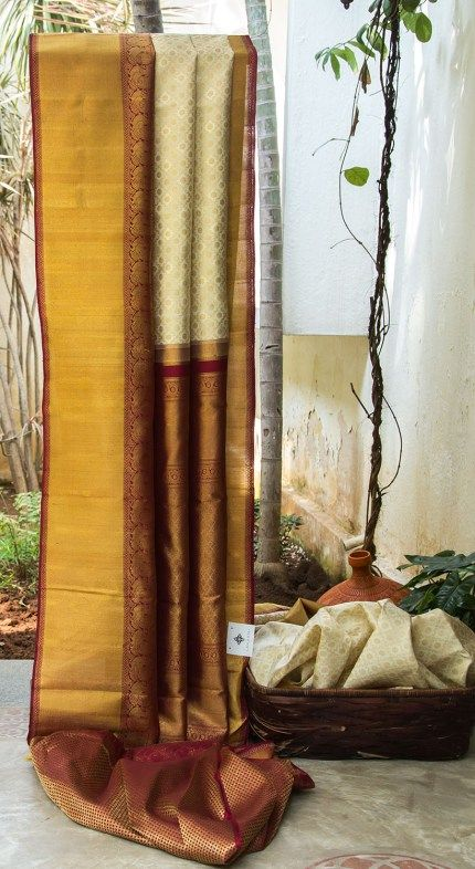 BEAUTIFUL OFF-WHITE WITH GOLD ZARI BUTTAS ALL OVER HAS CLASSIC MAROON WITH GOLD BORDER AND PALLU GIVES THE SAREE ROYAL FINISHING.