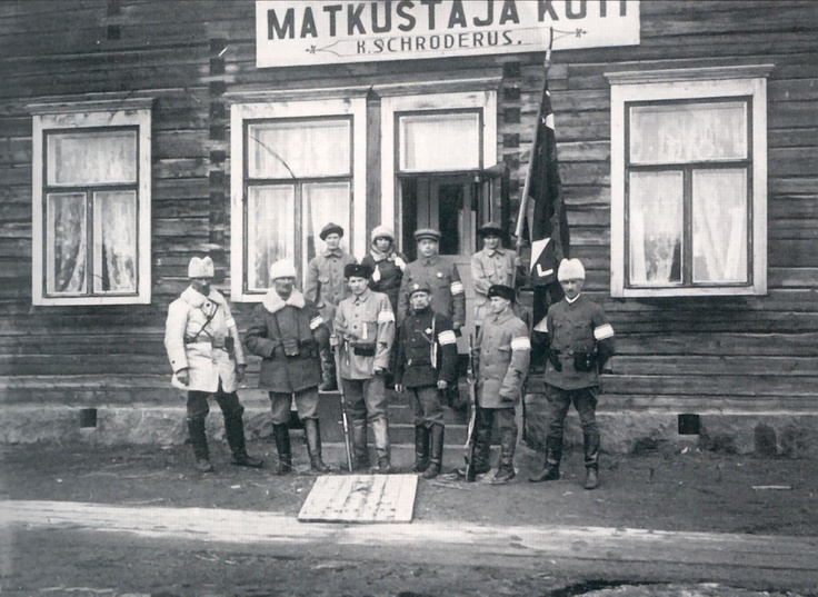 Leaders of the first Petsamo Expedition – Rovaniemi: 1918. Pictured left to right, front (in the white hat and coat): Thorsten Renvall (CO), Johan Bäckman, Julius Niemura, Jalmari Ruokokoski. Arvi Vinberg and Hjalmar Mehring. Rear: Ellen Id, Elvi Halle, Helge Aspelund, Ester Fogelberg, who is holding the flag created for the expedition by the artist, Jalmari Ruokokoski.