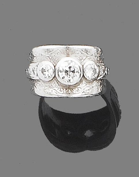 A diamond three-stone ring  The wide band with engraved foliate details, collet-set to the front with three graduated old brilliant-cut diamonds, diamonds approx. 1.00ct. total,