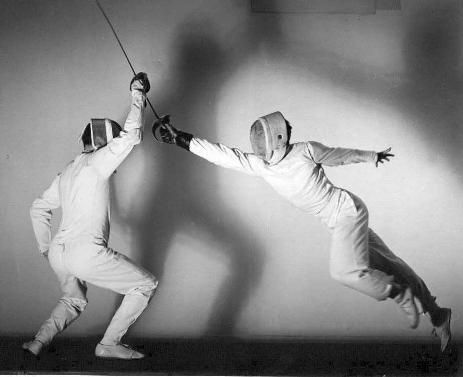 I love the way the shadows from both fencers looks so neat on the walls, theres a sense of duality considering they wear white uniforms while their shadows fight behind them. Grateful movement but with a fierce spirit in it.