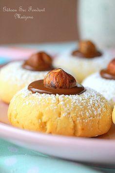 PETITS GATEAUX FONDANTS FOURRES CHOCO PRALINOISE (Pour 25 pièces : 250 g de beurre mou, 110 g de sucre glace, 15 g de sucre vanillé (2 sachets), 1 oeuf + 1 jaune d'oeuf, 75 g de Maïzena, 1/2 sachet de levure chimique (5 g), 320 à 350 g de farine, 1 bonne pincée de sel, noisettes ou amandes entières torréfiées, 100 g de pralinoise + 100 g de chocolat noir (ou 200 g de chocolat au lait), sucre glace pour saupoudrer)