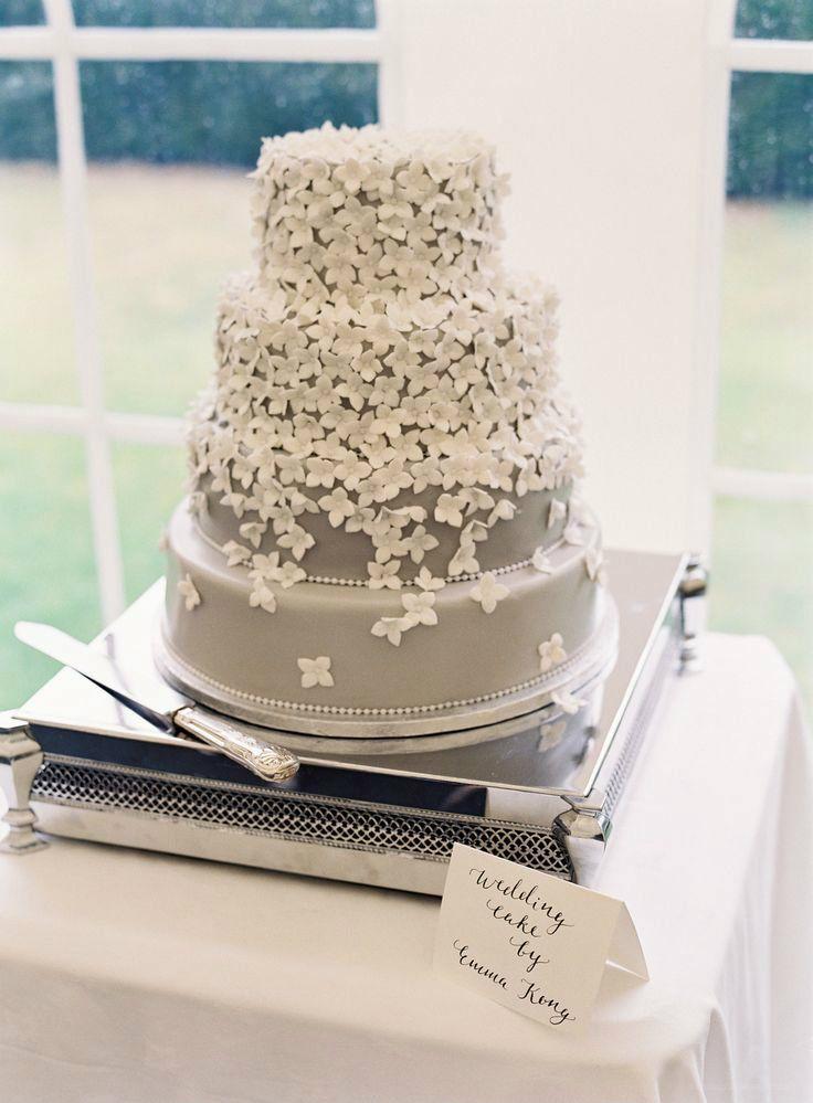 Hochzeitstorte mit grauem Fondant und vielen weißen Blüten