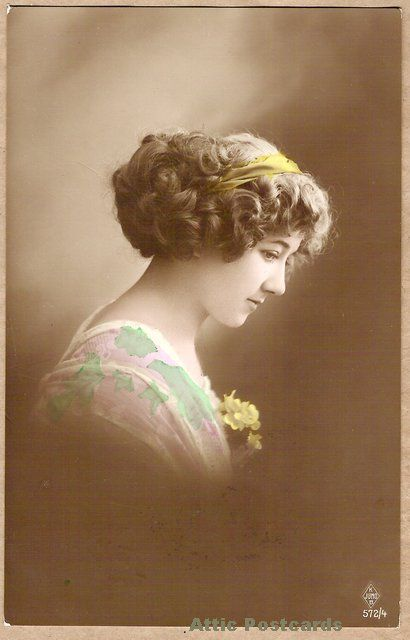 Vintage, hand coloured real photo postcard of a young woman in a headband and green and pink dress. 'K JUNO B' card.