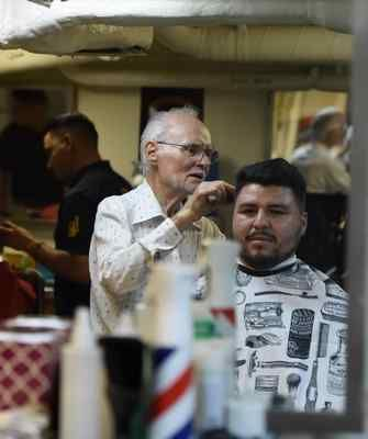 Barber Jack Smith cuts the hair of San Pedro resident David Saldana on board the Battleship IOWA in this July 2016 file photo. Battleship Iowa will open is barbershop again on Sunday, Jan. 22.   (Stephen Carr/The Daily Breeze/SCNG)