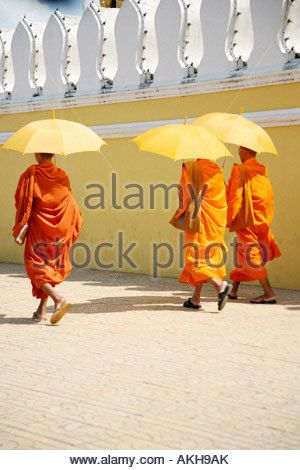 Monks Buddhists Grand Palace Phnom Penh Cambodia Cambodian buddhism history umbrella monk yellow orange robe capital politics - Stock Image
