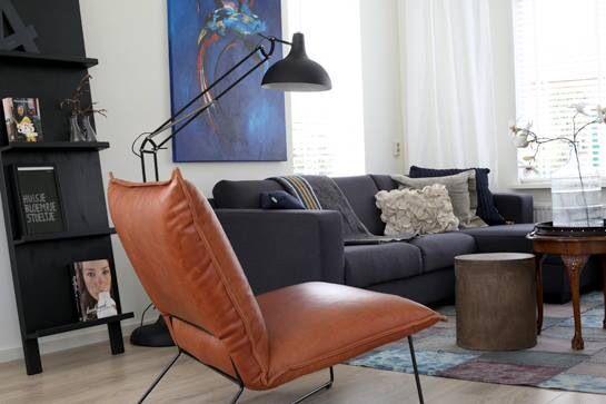 De stoeren leren fauteuil geeft een mooi contrast met de antraciet kleurige bank en al het wit.