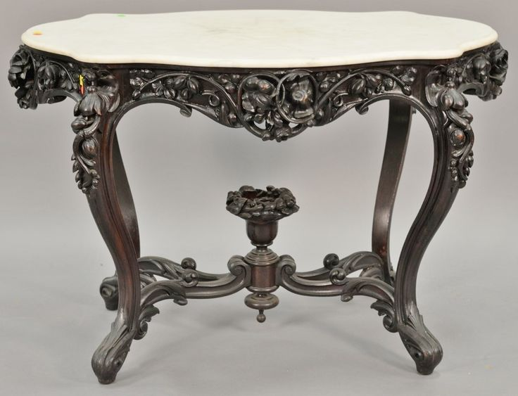 Rosewood Victorian center table having shaped marble top over highly carved three dimensional floral frieze and legs with floral carved center compote, in the manner of John Henry Belter, NY circa 1860.  Realized Price $4,200.00