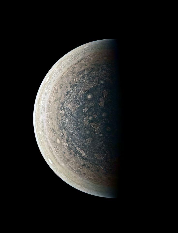 Jupiterov južný pól. Okolo pólu krúžia cyklóny a biele oválne búrky.