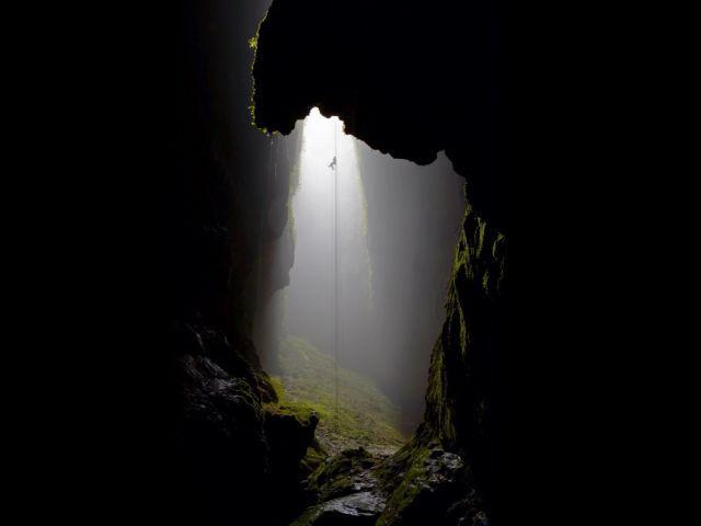 ニュージーランドのワイトモ洞窟でロープを下ろし降りているところ。