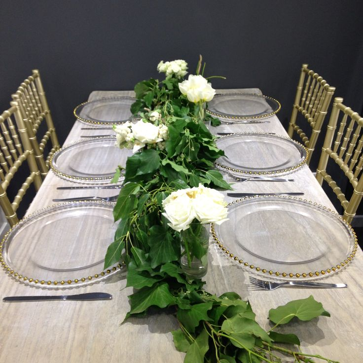 Centrepiece    A beautiful greenery centrepiece running down the middle of the table with touches of white, complimented by gold Tiffany chairs and gold beaded charger plates     Wedding reception     Wedding centrepiece     Wedding styling     Wedding decor