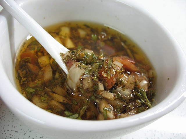 CHIMICHURRI  1/2 Cup Olive Oil  1/4 Cup Red Wine Vinegar  1/4 Cup Water  1 small bunch flat leaf-parsley; chopped (should equal about 1/2 cup)  1 medium onion; finely chopped  4 cloves garlic; finely minced  1/2 of a red bell pepper; seeded and finely diced  1 tomato; peeled, seeded, finely chopped  1 Tablespoon dried oregano  1 Tablespoon paprika  1 Teaspoon bay leaf (laurel); very small flakes  1 Tablespoon coarse salt  1 Teaspoon ground black pepper  hot chili flak