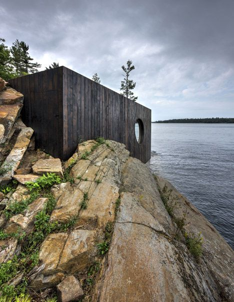 Lakeside sauna designed as a cavernous wooden grotto.