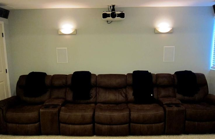 Basement home theater ideas. Mounted projector on ceiling with two wall sconces and Pioneer in-wall speakers. View the before and after pics of this DIY basement home theater finish! #hometheaterprojectordiy #hometheaterprojectorideas #hometheaterprojectormount