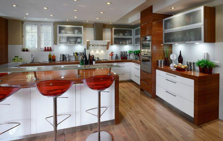 Bílá kuchyně PROGRES s horními prosklenými skříňkami. Zajímavě působí i samostatná skříň se spotřebiči, která není začleněna mezi vysoké potravinové skříně.