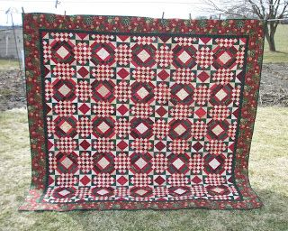 Red and green Carolina Crossroads quilt hanging on the clothesline in the backyard