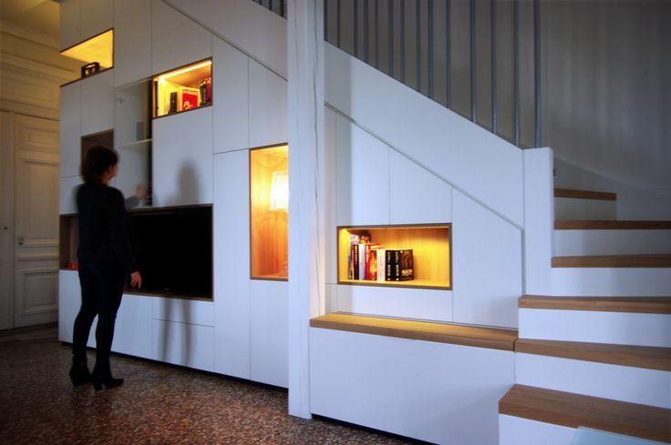 Intégrer des rangements, une bibliothèque, un espace HiFi /TV et une cave à vin dissimulée sous l'escalier   DanK Architectes  