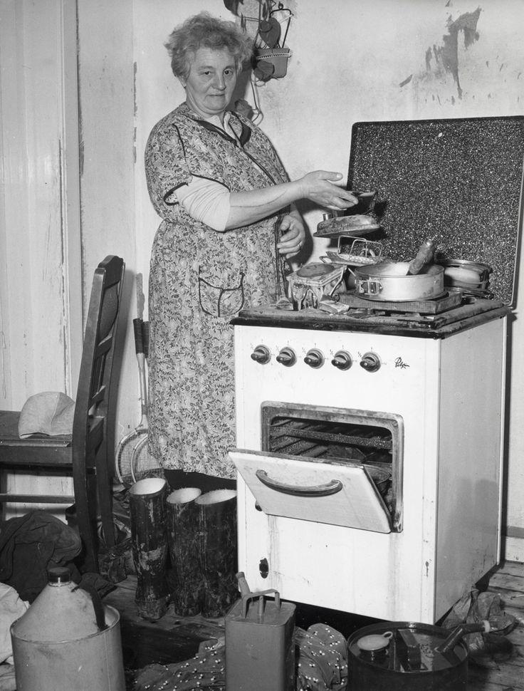 Huisvrouw naast gasfornuis in keuken, die door de dijkdoorbraak / watersnood / overstroming van Tuindorp Oostzaan ernstig heeft geleden, Nederland, 2 februari 1960. Er staan ook bemodderde laarzen.