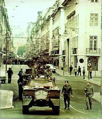 """1974 Carnation Revolution - Portuguese Army soldiers and armored cars of the left-wing revolutionary Armed Forces Movement (Movimento das Forças Armadas) mobilize on the streets of Lisbon in a coup d'etat against the Fascist """"Estado Novo"""" regime."""