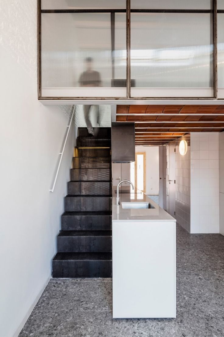 Natural light flows through the home from windows located at each end of the apartment and from a skylight in the gabled roof. The neutral, mostly white and grey palette keeps the space bright, with light bouncing off the walls and tiled surfaces.