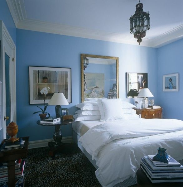a blue guest room with white linens and accents and leopard carpet in NYC designer Brian McCarthy's apartment