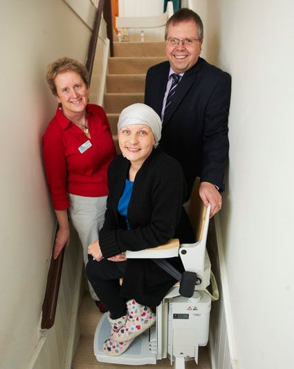 Lucy Moore (centre) on the donated stairlift at her home in Skipton with Sue Ryder Clinical Nurse Specialist Valerie Bone (left) and Acorn Stairlifts Company Secretary Dave Belmont (right)