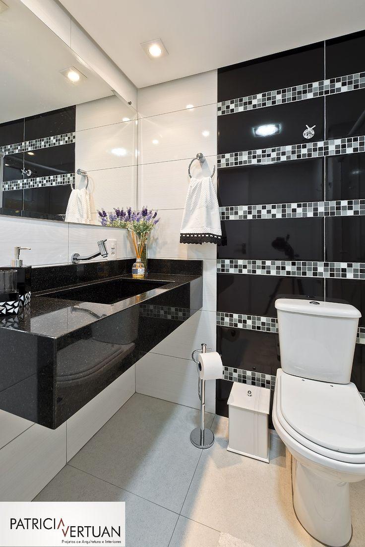 Banheiro social com cuba esculpida no tampo de granito preto São Gabriel. Revestimento em porcelanato preto e branco e mix de pastilhas de vidro.