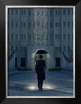 Man with Umbrella Under a Regional Rain Photographic Print by Joseph Hancock at Art.com