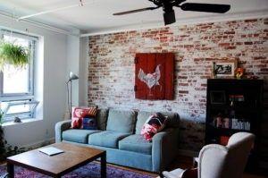 Eine Backstein-Mauer mit abgeschält weißen Kitteln zeigt ein Stück rot lackierten Holzfenster mit einem Gemälde einen weißen Hahn. Foto: Corynne Pless