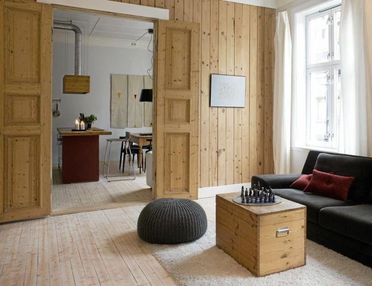Den gamle rupanelen er original, og var underlag for datidens tapet. Gulvet er slipt og oljet. Sofaen er fra SofaSoGood, mens puffen Urchin er fra These flocks. I bakgrunnene synes kjøkkenet med innredning fra HTH og barkrakker fra Ikea.