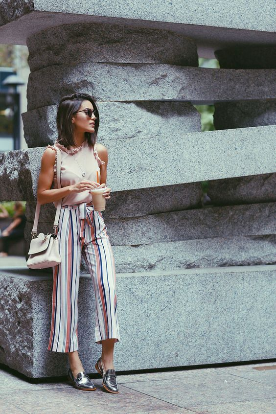 Camila Coelho during NYFW on her way to watch Akris fashion show wearing colorful striped pantacourt, a blush sleeveless with ruffles top, and metallic oxfords. A caminho do show de Akris usando pantacourt listrada, uma regata com babados e oxfords metalizados.: