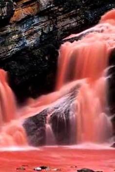 This is Cameron Falls in Waterton Lakes National Park in Canada. And yes this is real! A rare phenomenon occurs during heavy rain to create the red color!