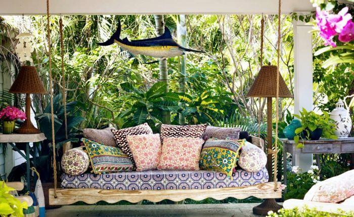 terrasse couverte avec une balançoire et coussins en tant que déco