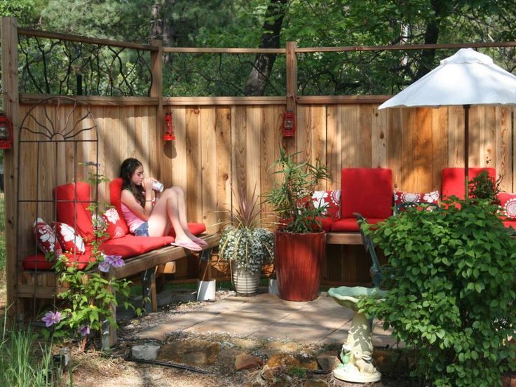 Red accents brighten a Southwestern garden room with cozy cushioned benches.