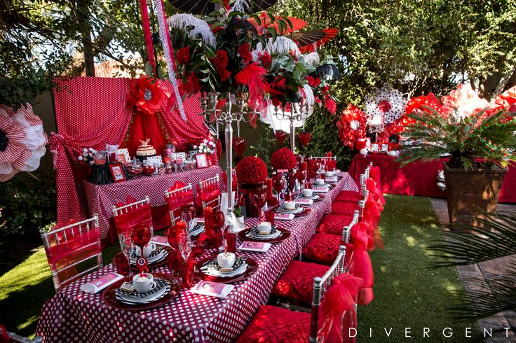 Red, Black and White themed garden birthday party set up with giant paper flowers, feather and flower centre-pieces