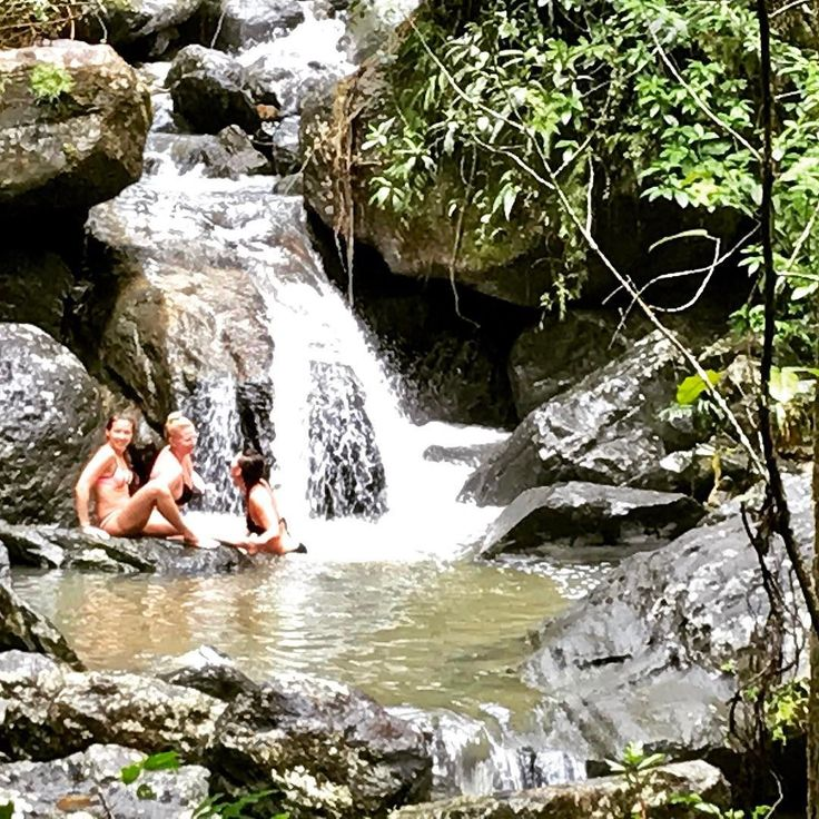 Bikini clad girls splashing at a waterfall in El Yunque National Forest. #elyunquerainforest #livecolorfully #meetpuertorico #elconresort #waterfalls