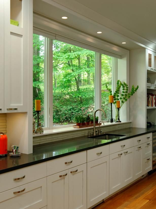 HGTV presents a contemporary galley kitchen with large windows, white open shelving, white cabinets, black quartz countertop and undermount sink.
