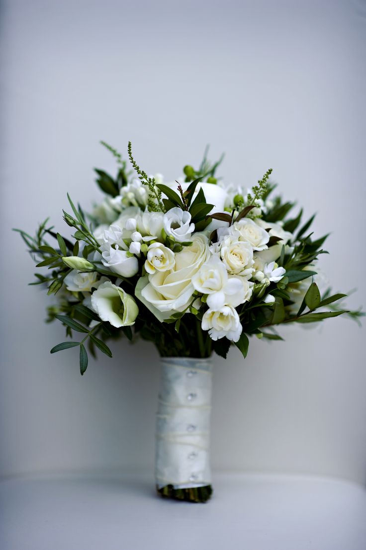 A stylish white and green bridal bouquet beautifully tied in white silk ribbon