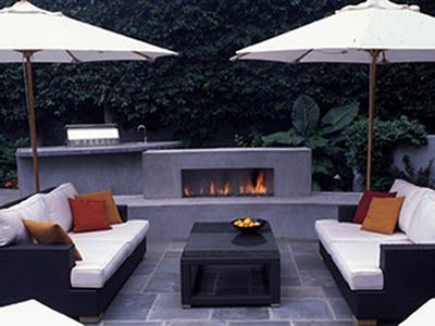 modern patio with fireplace, umbrellas, outdoor kitchen