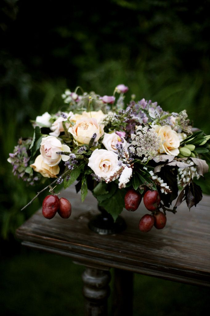 moody, cascading arrangement of roses, Queen Anne's lace, pieris and stonefruit by McKenzie Powell