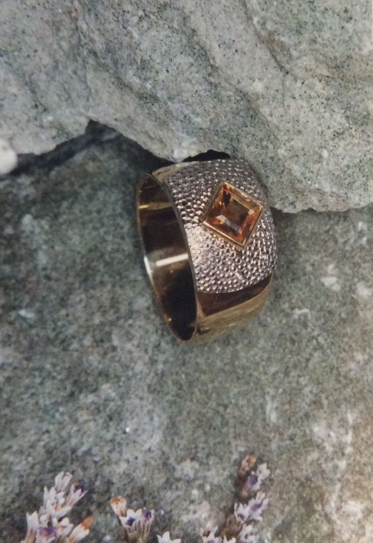 ring featuring imperial topaz rim set and placed on a texture of white gold inlaid into a wide yellow gold band