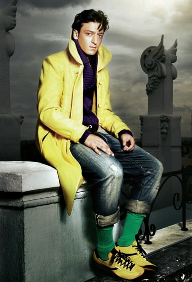 This is football/soccer player Mesut Ozil. He's wearing yellow shoes worn with green socks and a yellow jacket with a purple knitted top & jeans