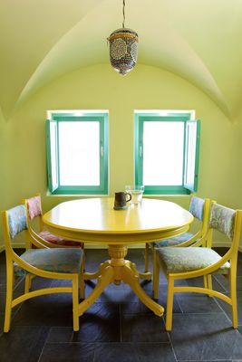 Stylish-Dinningroom-Yellow-Turqoise-Wooden-Table-Chairs-Tiles-Santorini-Island-Greece