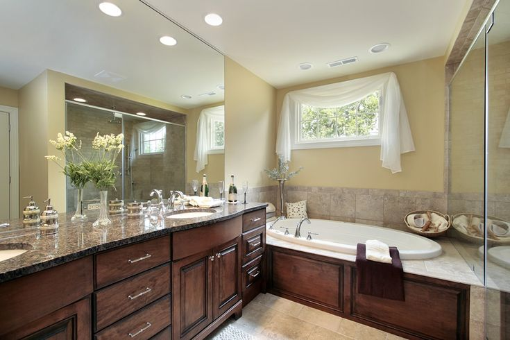 This a medium sized kitchen maple wood cabinets. The dark wooden vanity has a granite countertop. The bathroom uses a large frameless mirror. The shower area uses glass mosaic tiles and light cream walls.