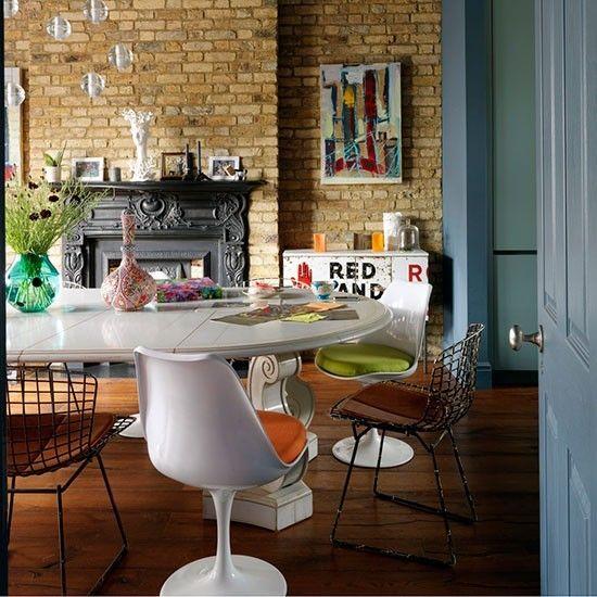 Столовая с викторианским камином, кирпичной стеной и эклектичной мебелью. .
