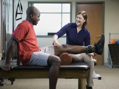 Female physical therapist assisting man with leg exercise - Andersen Ross / Getty Images