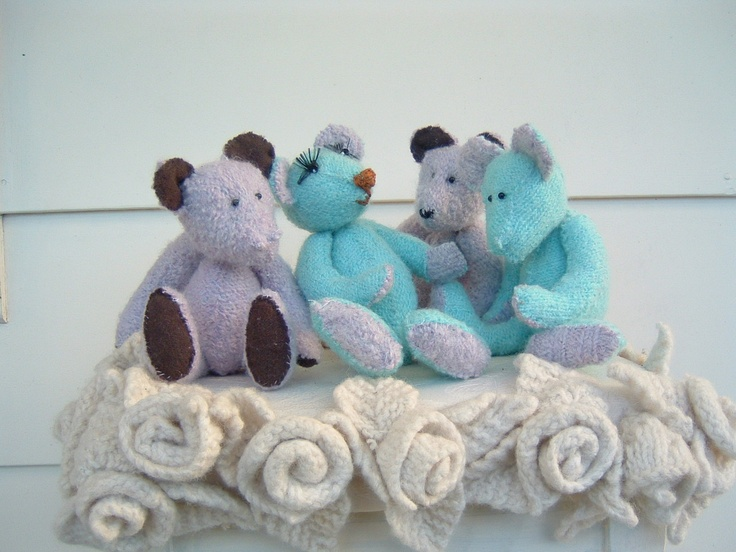 Bears made ot of Felted jumpers sitting on a footstool covered in hand knitted roses