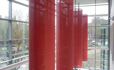 TOWER WHARF -  Bristol -UK - 'floating' interior fabric sculptures. The four gigantic fabric cylinders, each measuring 1100 diameter x 4800mm high are made with Soltis 86 Screen. While the Soltis screen sculptures are stylish, they also help break the vast space acoustically, while diffusing the sunlight from the glazed wall.