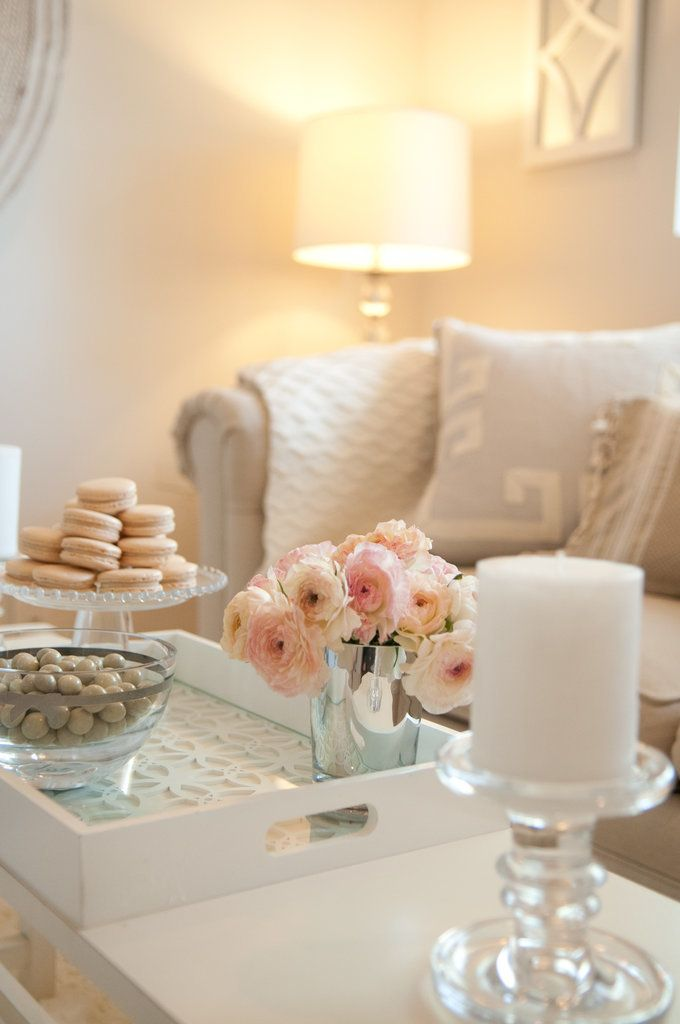 A neutral living room accented with candles, mirrors and glass accessories.