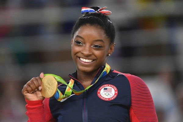 US gymnast Simone Biles celebrates on the podium of the women's floor event final of the Artistic Gymnastics at the Olympic Arena during the Rio 2016 Olympic Games in Rio de Janeiro on August 16, 2016. / AFP / Toshifumi KITAMURA